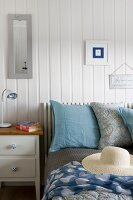 Large pillows and straw hat on bed next to white-painted bedside cabinet against white wooden wall