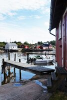 Wooden jetties and wooden houses, some painted red, on river banks