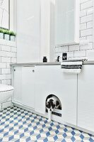 White bathroom with tiled walls & floor, wall-mounted cabinets & cat flap in sliding door of base unit