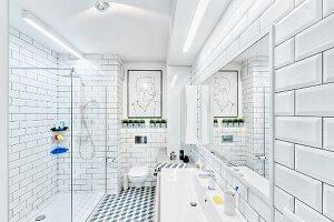 White, modern bathroom with tiled walls & floor, strip lights over washstand & glazed, floor-level shower; modern artwork above wall-mounted toilet