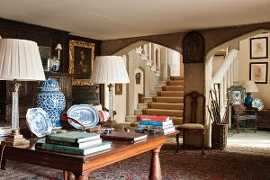 Jacobean manor house with stone Tudor arches, Chinese lidded jars, plates and lamps with crystal bases on mahogany table in foyer
