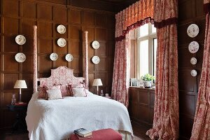 Toile-de-jouy curtains and double bed with ornate headboard in wood-panelled bedroom with decorative china plates on walls