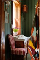 Chair with striped cover against dark green striped wallpaper in bathroom with antique-style washstand below window