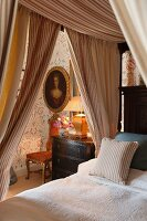 Antique portrait, antique chest of drawers, floral wallpaper and four-poster bed with striped curtains in foreground