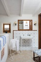 Delicate washstand against blue and white tiled wall and white towels on vintage-style towel rail in bathroom