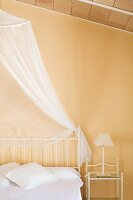 Bed with delicate, white metal frame and airy canopy in bedroom with pastel yellow wall