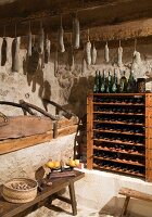 Wine rack and home-made salami hanging from wooden beams in rustic pantry