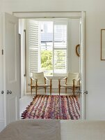 Open double doors with view of colourful rug and delicate armchairs with ecru covers below window