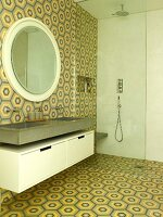 Washstand, round mirror, floor-level shower with glass screen in bathroom with retro tiles on wall and floor