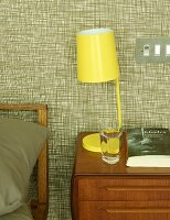 Yellow, retro bedside lamp on wooden bedside cabinet against wallpapered wall