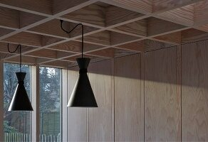 Retro pendant lamps with black metal lampshades suspended from modern coffered ceiling in pale larch wood and sunlight falling on wood-panelled wall