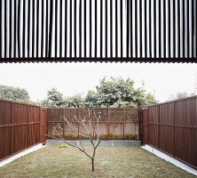 Small, austere, enclosed garden of modern Indian house with delicate wooden fences and sun screen element above