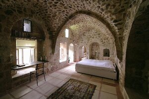 Old house with limestone walls and vaulted ceilings; large bed in open-plan bedroom and improvised work area in front of window