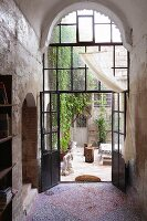 Foyer with tall, arched steel and glass door and view into courtyard of old house