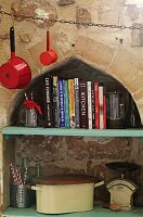 Cookery books and vintage kitchen utensils on shelf in niche with ogee arch