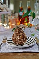 Decorated pear with name tag as festive table ornament on black and white plate