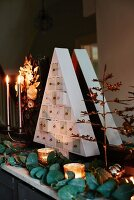 Triangular, fir-tree-shaped chest of tiny drawers as perpetual Advent calendar arranged on mantelpiece with plants and candles