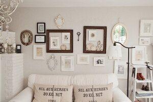 Weisses Polstersofa mit Kissen aus Leinensäcken, vor Wand mit Bildern und Bilderrahmen