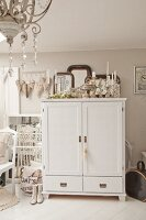 Collection of silver candlesticks on top of white-painted cabinet next to heart ornaments on pastel wall