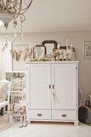Weiss lackierter Schrank, obenauf Sammlung von Silber Kerzenhalter, seitlich Dekoherzen an pastellfarbener Wand