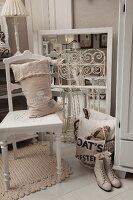 Leinensack auf weiss lackierten, Küchenstuhl, seitlich Vintage Damen Schnürstiefel und nostalgische Flohmarktartikel auf weiss lackiertem Dielenboden
