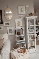 Shabby Kleinmöbel vor pastellfarbener Wand und aufgehängten Bildern