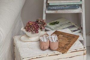 Getrocknete Hortensien in weissem Porzellan und rosa Balettschue auf Spitzendeckchen