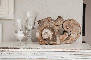 Vintage Architekturelemente, schneckenförmige Holzarbeiten und Windlichter aus Glas auf Ablage
