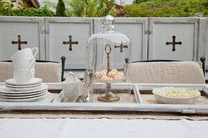 Geschirr und Baisergebäck unter Glashaube in ausgebautem Fensterrahmen auf Tisch