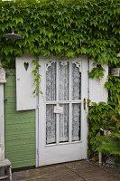 Tür mit Spitzenvorhang hinter Glasfüllung eines Holzhäuschen und berankte Holzfassade