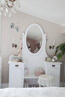 Weisser Schminktisch mit ovalem Spiegel an pastellgrau getönter Wand im Schlafzimmer
