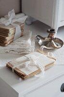 Mit Spitzenband verschnürte Briefe und Vintage Kerzenhalter in Silber