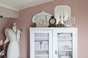 Weisse Wäscheschrank mit Glastür, obenauf Vintage Kerzenhalter, seitlich Schneiderpuppe