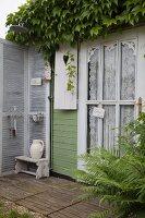 Ausschnitt eines Holzhäuschens mit berankter Hausfassade, an Tür Spitzenvorhang, kleine Terrasse mit Waschecke vor Paravent