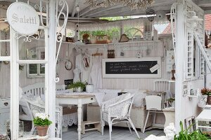 Shabby-chic summer house with pale furniture and flea-market accessories