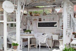 Shabby Gartenpavillon mit hellen Möbeln und Flohmarktartikeln