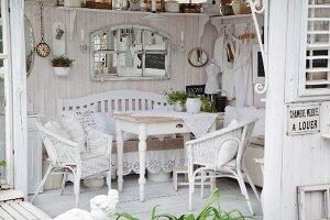 Blick auf Holztisch und weisse Rattanstühle in Shabby Gartenpavillon mit weiss lasierten Holzwänden