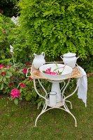 Vintage Metallgestell mit Waschschüssel und Krug im Garten