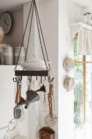 Von Decke abgehängter Metallkranz mit Haken, darauf Küchenutensilien, in ländlicher Küche