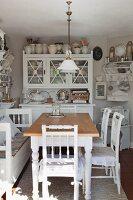 Ländlicher Esstisch mit weissen Holzstühlen, im Hintergrund Anrichte in gemütlicher Wohnküche