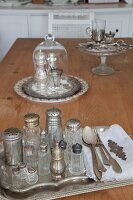 Vintage salt cellars on silver tray and salt and pepper shakers under glass cover on wooden table
