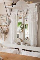Dekoriertes Fenster mit weissen Spitzenvorhängen, im Vordergrund alte, verstellbare Pendelleuchte mit weissem Porzellanschirm