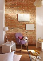 Fifties armchair with lilac cover and lamp on modern, white side table against brick wall