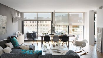 View across sofa combination to dining set with Eames Chairs in front of glass wall in penthouse apartment