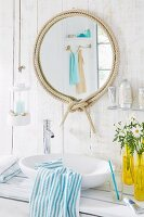 Round bathroom mirror with decorative rope frame in a white bathroom with wood-panelled walls