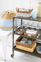 Wicker baskets, glasses, cups and crockery on a serving trolley