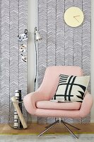 A pastel pink swivel chair contrasting with the geographic black-and-white patterns on the wallpapered wooden panels and cushion