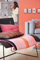 A living room with upholstered seats in black and grey complemented by a mixture of patterns in pink and coral