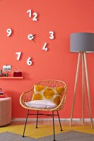 A wicker 1950s-style chair and a mustard yellow rug against a coral wall with an unconventional clock