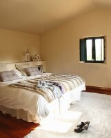 Double bed with fur blanket and white bed linen in minimalist attic bedroom